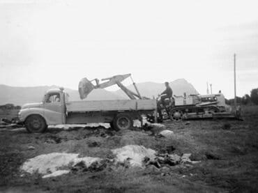 Gammelt bilde av personer som står ved siden av en gammel lastebil